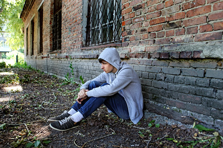 Sad Teenager sit on the Brick Building Background