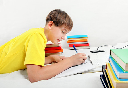 Kid doing Homework on the Bed in the Room