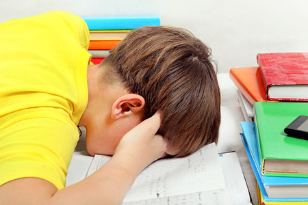 Tired Kid doing Homework on the Bed in the Room Banque d'images