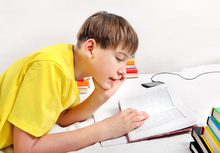 outwork: Kid doing Homework on the Bed in the Room