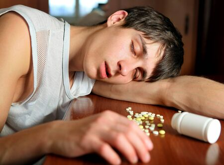 somnolent: Young Man sleep near the Pills on the Table at the Home
