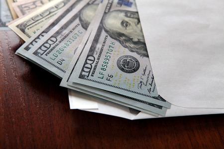 テーブルのクローズ アップに封筒で米ドル
