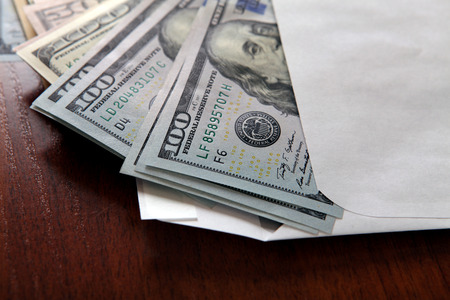 cash money: Dólares estadounidenses en el sobre en la mesa primer plano Foto de archivo