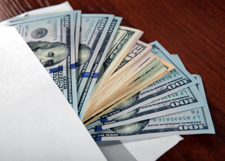 payola: American Dollars in the Envelope on the Table closeup Stock Photo