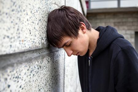 슬픈 젊은이 야외에서 벽에 스톡 콘텐츠