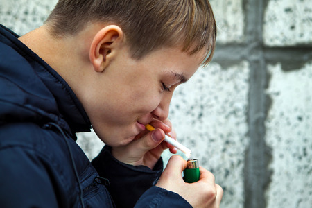 Teenager secretly smoke the Cigarette on the Street