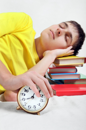 reveille: Teenager sleep on the Books with Alarm Clock. Focus on the Clock