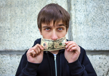 trade secret: Young Man close the Mouth with American Dollars by the Wall