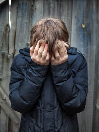 personas tristes: Adolescente triste en el fondo de la pared de madera