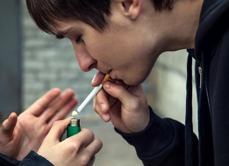 hombre fumando: El hombre joven fuma el cigarrillo en la calle Foto de archivo