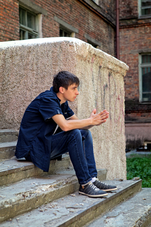 expulsion: Sad Young Man sit on the City Street