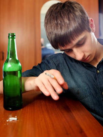the weariness: Tired Young Man sleep with Bottle of the Beer and Cigarette at the Home