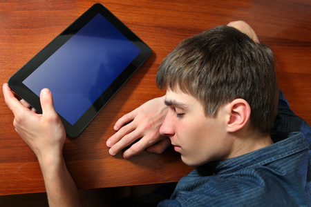 drowse: Tired Young Man sleep with Tablet Computer on the Table Stock Photo