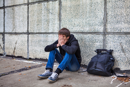 despondent: Sad Young Man sit by the Wall on the Street