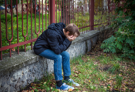 sorrowful: Sorrowful Kid sit on the City Street