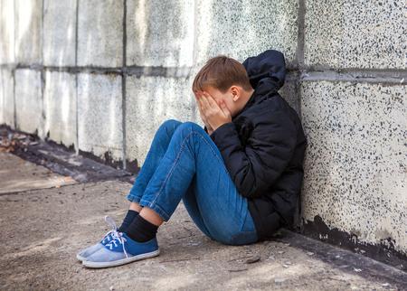 vagabundos: Kid triste sentarse junto a la pared en la calle Foto de archivo