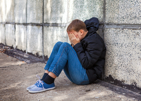 Sad Kid sit by the Wall on the Street Stock Photo