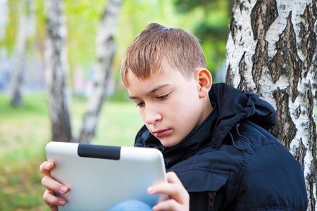 doleful: Pensive Teenager with Tablet Computer in the Autumn Park