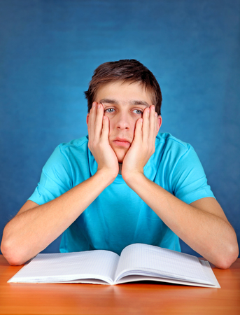school exam: Sorrowful Student at the School Desk on the Blue Background
