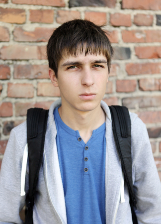 doleful: Sad Young Man on the Brick Wall Background Stock Photo