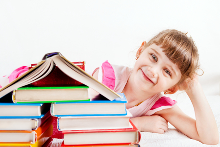 bibliophile: Cheerful Little Girl with the Books on the White Wall Background