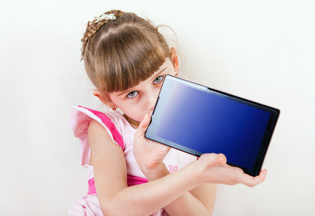 one child: Little Girl show Tablet Computer on White Wall Background Stock Photo