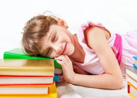 bibliophile: Happy Little Girl Resting on the Books on the White Background Stock Photo