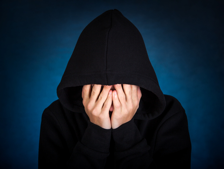 tearful: Sad Man in the Hood on the Dark Background