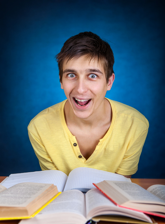 gladden: Surprised Student with the Book on the School Desk Stock Photo