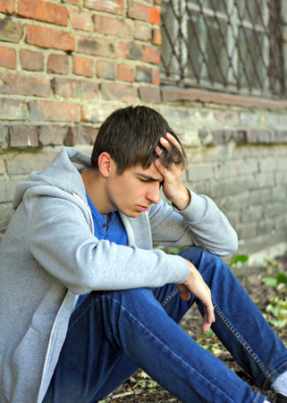 doleful: Sad Young Man sit near the Brick Wall of the Old House