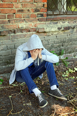 doleful: Sad Young Man near the Brick Wall of the Old House