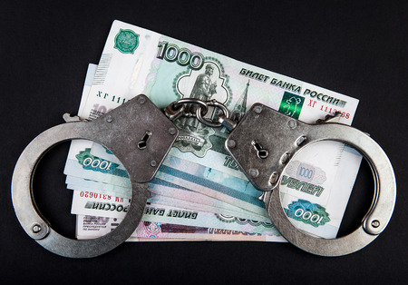 venal: Russian Rubles and Handcuffs on the Black Background Stock Photo