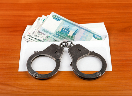 manacles: Handcuffs on the Envelope with Russian Rubles on the Table