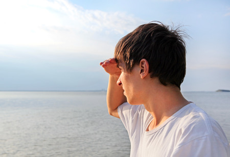 alarming: Young Man to gaze into the distance at the Seaside Stock Photo