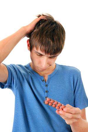 hesitant: Hesitant Young Man with the Pills Isolated on the White Background