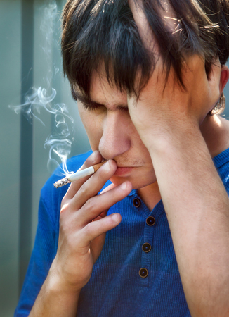 sorrowful: Sorrowful Young Man with Cigarette on the Street