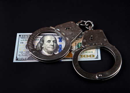 manacles: American Dollars and Handcuffs on the Black Background Stock Photo