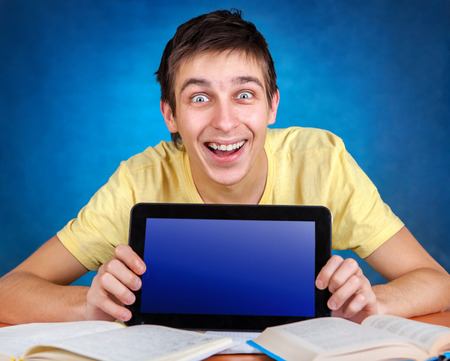 gladden: Surprised Young Man with Tablet on the Blue Background