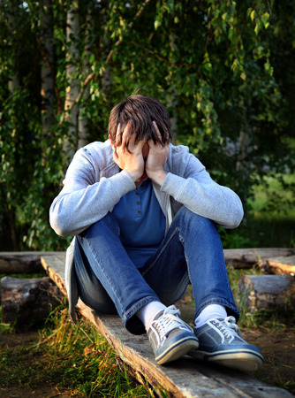 tearful: Sad Young Man sit on the Log outdoor