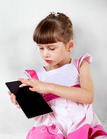 one child: Small Girl with Tablet Computer on White Wall Background