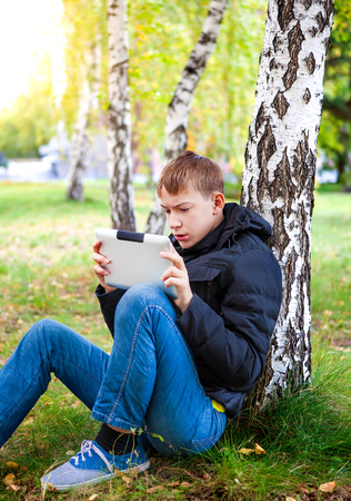Pensive Teenager with Tablet Computer in the Autumn Park