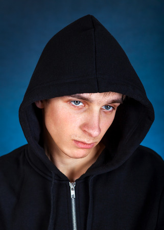 cassock: Sad Young Man in the Hood on the Dark Background