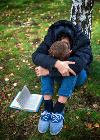Sad Teenager with the Book in the Autumn Park photo