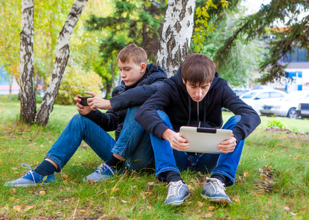 spat: Sad Boys with Gadgets sit under Tree in the Autumn Park