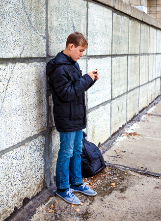 Teenager with Cellphone on the City Street photo