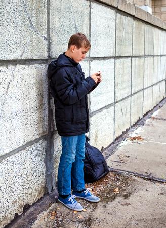 boyhood: Teenager with Cellphone on the City Street