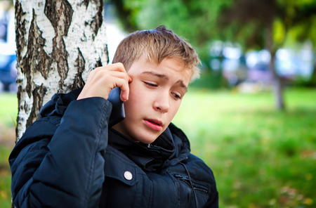 Stressed Teenager with Cellphone in the Park photo