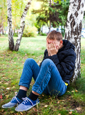 Sad Teenager sit under Tree in the Park