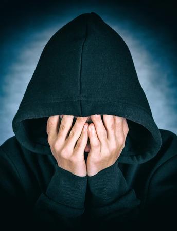 sotana: Vignetting Photo of Sad Man in the Hood on the Dark Background