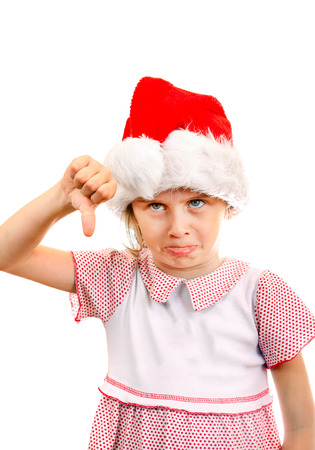 irritate: Annoyed Small Girl in Santa Hat make Thumb Down on the White Background